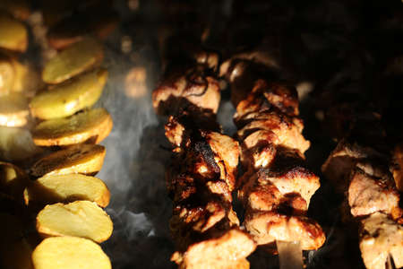meat skewers: Photo closeup of delicious hot potatoes and meat skewers cooked on grill charbroiled barbecue on brazier on blurred smoky background, horizontal picture Stock Photo