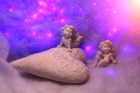 soulful: Closeup of beautiful soulful figurine composition of cupid angels for valentine day or christmas with small pillow in shape of heart lying on white wadding decorating snow with purple light sparks