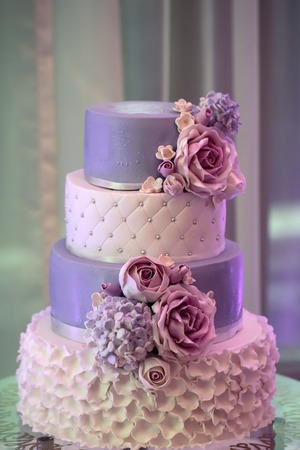 tiers: Photo closeup of traditional elegant delicious sweet four-layer wedding cake decorated with butter-cream roses on glass stand on blurred violet background, vertical picture Stock Photo
