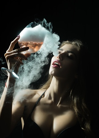 elixir: Closeup view portrait of one beautiful young sensual serious enigmatic enchanted woman holding in hand drinking glass full of liquid with smoke of magic elixir of beuty and life and secret of youth