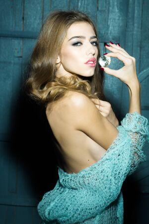 elixir: Uno encantado enigmática mujer hermosa joven sensual con el pelo largo y rizado exuberante en paño azul de punto mantiene gran magia blanca piedra facetas gema preciosa como elixir de la juventud y la belleza, imagen vertical