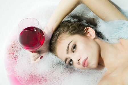 relaxion: Closeup view portrat of attractive young sexy girl with wet hair lying in white bath tab full of water and soap foam holding drinking glass with red liquid as elixir of beauty or desert wine indoor