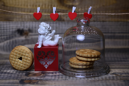 putto: Closeup of beautiful cupid angel decorative figurine on red paper greeting valentine box and hanging clothes-peg with round cookie under glass flask on wooden background, horizontal picture