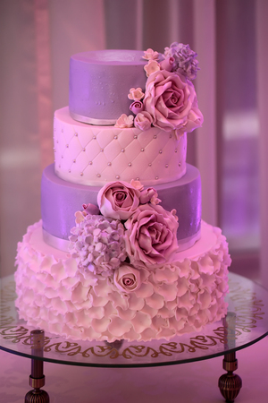 receptions: Photo closeup of traditional elegant delicious sweet four-layer wedding cake decorated with butter-cream roses on glass stand on blurred violet background, vertical picture Stock Photo