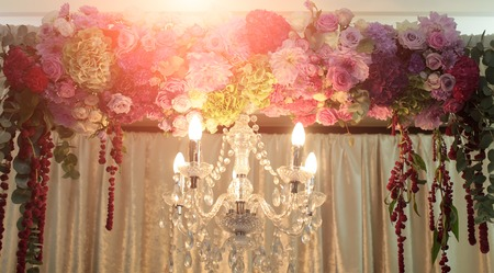 electric fixture: Photo closeup of one classic cut-glass crystal chandelier lighting fixture with electric opal bulbs illuminating and arch decorated with fresh flowers on white curtains background, horizontal picture