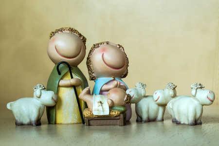 jesus standing: Closeup view of decorative celbrating Christmas and Jesus birth figurines of holy vergin Mary Josepd newborn child with few white sheeps standing on light leather background, horizontal picture Stock Photo