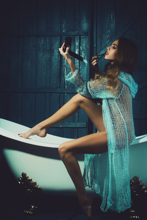 One beautiful sensual glamour fashionable young fairy woman with long hair in blue knitted cloth sitting on white bath tub making makeup with cosmetics indoor on wooden background, vertical picture