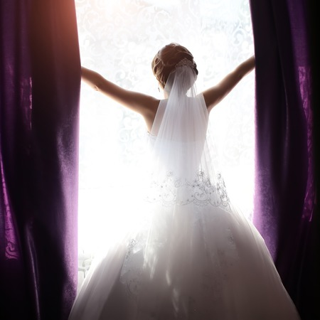 window opening: Photo of young bride full length back view wearing long lace white wedding dress and bridal veil standing in bright daylight window opening on lighted background, square picture Stock Photo