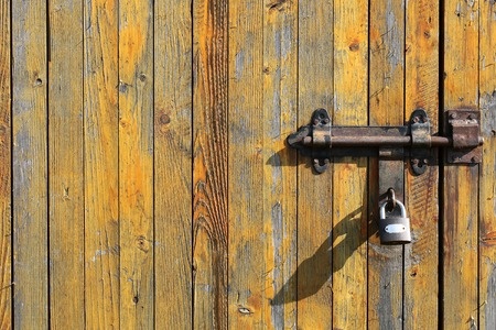 loosing: Photo padlock on of old gate and close boarded fence wooden palisade wood boards with knots loosing yellow paint on timber background, horizontal picture