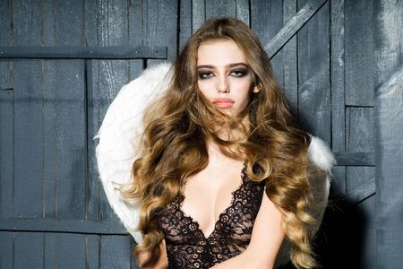 hair feathers: One beautiful tender dreaming young fashionable woman with long curly hair bright makeup and white fluffy angel wings with white feathers on back in black lace dress on wooden background, horizontal Stock Photo