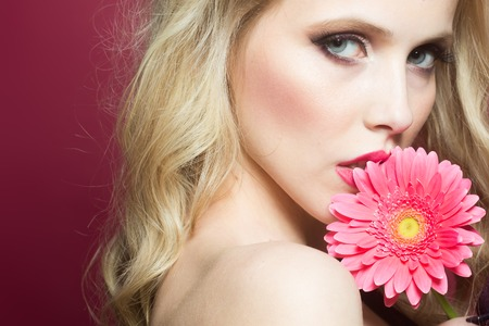brigt: Closeup portrait of one beautiful sexy passionate blonde woman with long curly hair in studio with bare shoulder and brigt makeup holding gerbera flower near face on pink backdrop, horizontal picture