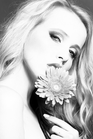 brigt: Closeup portrait of one beautiful sexy passionate blonde woman with long curly hair in studio with bare shoulder and brigt makeup holding gerbera flower near face black and white, vertical picture
