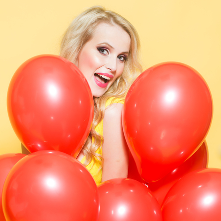flirtatious: One beautiful smiling flirtatious young happy blond woman with long curly hair standing in bunch of red party balloons in studio on yellow backdrop, square picture Stock Photo