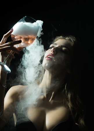 elixir: Primer retrato de vista de un solo hermosa sensual seria Mujer encantada enigmática joven que sostiene en la mano vaso lleno de líquido con el humo del elixir mágico de beuty y la vida y el secreto de la juventud
