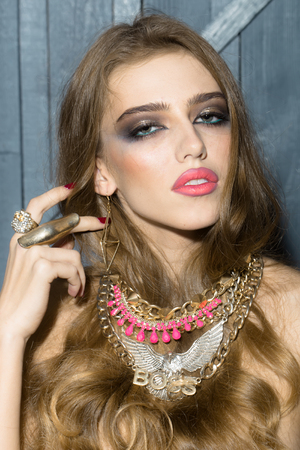 costume jewellery: Pretty sensual glamour young fashionable girl with long curly hair bright makeup and many colorful different costume jewellery of necklace rings and earrings on wooden background, vertical picture