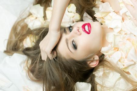 mujer con rosas: Primer retrato de vista de un solo joven y bella mujer de glamour moda apasionada con brillo de labios rojos y el pelo de seda ganas tumbado en pastel luz amarillo pétalos de flores de rosa, foto horizontal