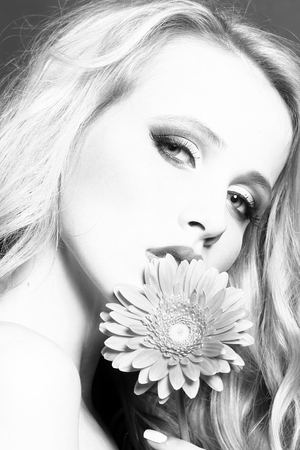 Closeup portrait of one beautiful sexy passionate blonde woman with long curly hair in studio with bare shoulder and brigt makeup holding gerbera flower near face black and white, vertical picture