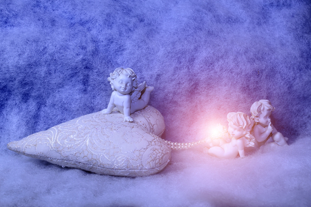 soulful: Closeup of beautiful soulful figurine composition of cupid angels for valentine day or christmas with small pillow in shape of heart lying on white wadding decorating snow with bright light spark