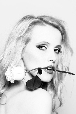 Closeup portrait of one beautiful sexy passionate blonde woman with long curly hair in studio with bare shoulder and brigt makeup holding rose flower in mouth black and white, vertical picture Imagens