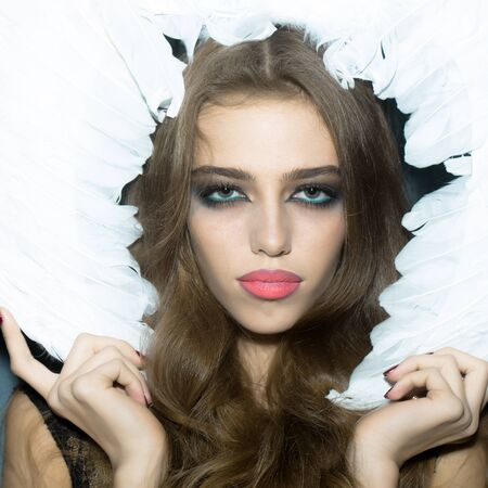 hair feathers: One beautiful tender dreaming young fashionable woman with long curly hair bright makeup and frame of white fluffy angel wings with feathers, square picture