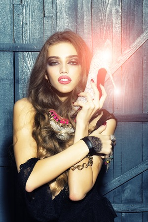 costume jewellery: Attractive glamour young fashionable girl with long curly hair bright makeup and costume jewellery of necklace rings and earrings holding diamond shoe with red sole on wooden background, vertical Stock Photo