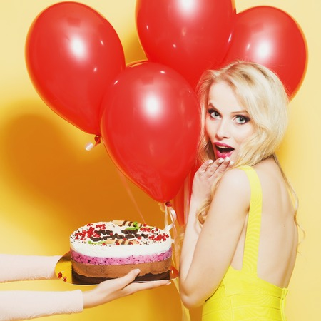 One attractive smiling young happy blond woman with long curly hair with birthday cake with candle in female hand near bunch of red party balloons in studio on yellow backdrop, square picture Stok Fotoğraf