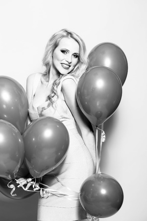 flirtatious: One beautiful smiling flirtatious young happy blond woman with long curly hair standing in bunch of many party balloons in studio black and white, vertical picture Stock Photo