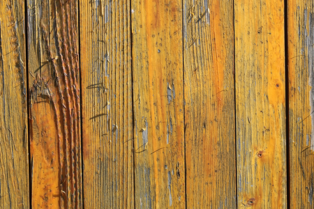 loosing: Photo closeup of old close boarded fence wooden palisade wood boards with knots loosing yellow paint on timber background, horizontal picture