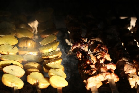 charbroiled: Photo closeup of delicious hot potatoes and meat skewers cooked on grill charbroiled barbecue on brazier on blurred smoky background, horizontal picture Stock Photo