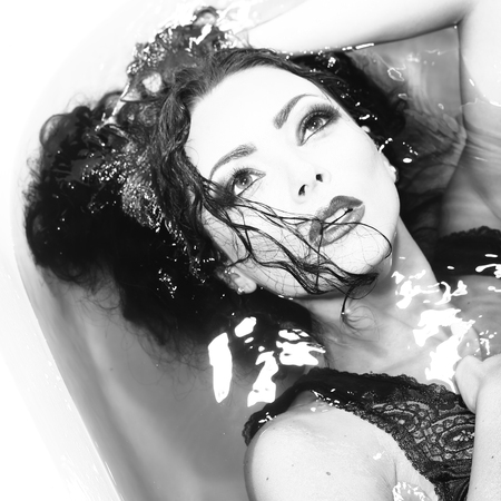 lying in bathtub: Closeup of one sexual young sensory attractive brunette woman with wet long curly hair and bright makeup lying in bath tab full of water taking shower in cloth black and white, square picture