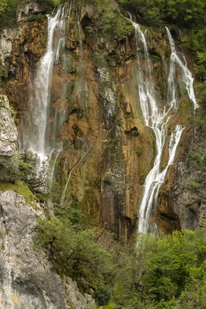 falling down: Photo of beautiful waterfalls cascades falling down from mountain wall rock surrounded by picturesque green rich foliage on natural landscape background, vertictal picture Stock Photo