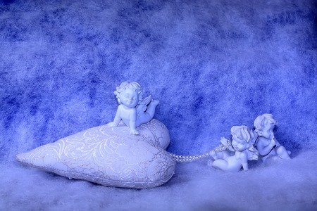 soulful: Closeup of beautiful soulful figurine composition of cupid angels for valentine day or christmas with small pillow in shape of heart lying on white wadding decorating snow, horizontal picture