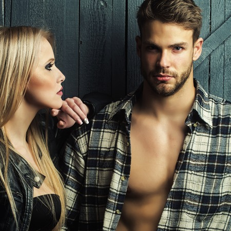 sexy breasts: Young sexual couple of pretty blonde woman in leather jacket standing near handsome serious man in checkered shirt with bare muscular chest in studio on wooden background, square picture Stock Photo