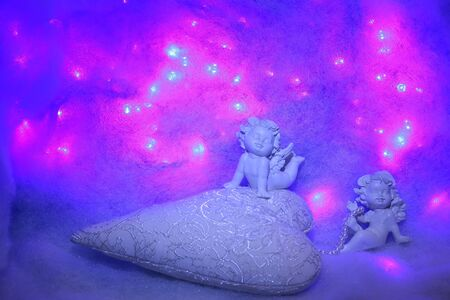 wadding: Closeup of beautiful soulful figurine composition of cupid angels for valentine day or christmas with small pillow in shape of heart lying on white wadding decorating snow with purple light sparks