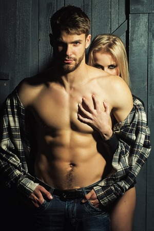 bare breast: Young sexual couple of handsome serious man in checkered shirt with bare muscular chest standing before pretty blonde woman embracing and touching breast in studio, vertical picture Stock Photo