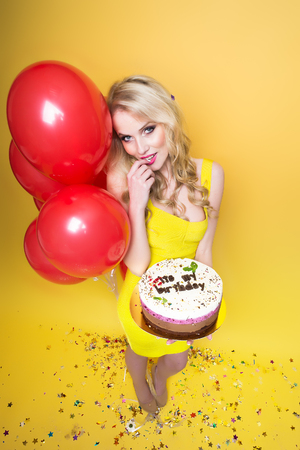 flirtatious: One pretty emotional young flirtatious blonde girl with long curly hair holding birthday cake with candles near bunch of red balloons with confetti indoor in studio on yellow backdrop, vertical photo