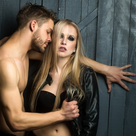 bare breast: Young sexual couple of handsome serious man with bare muscular chest standing undressing pretty blonde woman standing and touching breast in studio, square picture Stock Photo