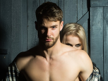 bare breast: Young sexual couple of handsome serious man in checkered shirt with bare muscular chest standing before pretty blonde woman embracing and touching breast in studio, horizontal picture