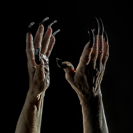 female devil: Closeup view of two female old scary mystic hands with long black nails on fingers of witch zomby demon or devil on halloween holiday character in studio indoor on dark background, square picture Stock Photo