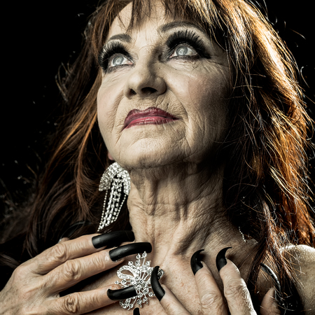 hag: One old scary smiling witch woman with long red knotty hair in blouse with black long nails on hand as halloween character with bright makeup in studio on black background, square photo Stock Photo