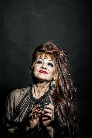 One old scary smiling witch woman with long red knotty hair in blouse with black long nails on hand as halloween character with bright makeup in studio on black background, vertical photo