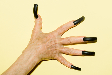female devil: Closeup view of one female old mystic hand with long black nails on fingers of witch zomby demon or devil on halloween holiday character in studio indoor on light yellow background, horizontal picture