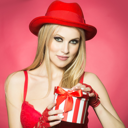 winter gift: One attractive sexual happy smiling young blonde woman with long hair in red hat gloves and bra holding roung present box for christmas valentine or new year on pink backdrop, square picture