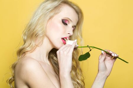 brigt: Closeup portrait of one beautiful sexy passionate blonde woman with long curly hair in studio with bare shoulder and brigt makeup holding rose flower near face on yellow backdrop, horizontal picture Stock Photo