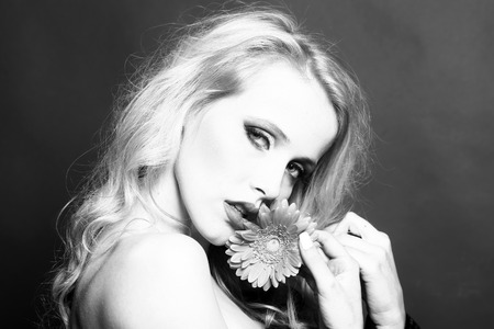 brigt: Closeup portrait of one beautiful sexy passionate blonde woman with long curly hair in studio with bare shoulder and brigt makeup holding gerbera flower near face black and white, horizontal picture Stock Photo