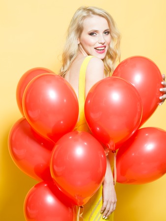 flirtatious: One beautiful smiling flirtatious young happy blond woman with long curly hair standing in bunch of red party balloons in studio on yellow backdrop, vertical picture