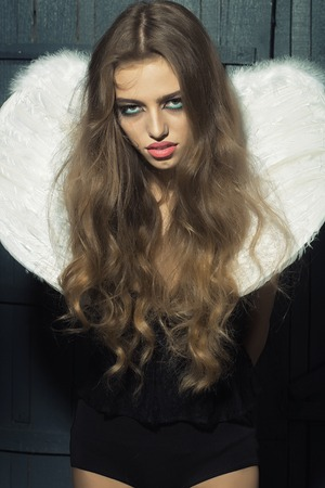 hair feathers: One beautiful tender dreaming young fashionable woman with long curly hair bright makeup and white fluffy angel wings with white feathers on back in black cloth dress on wooden background, vertical