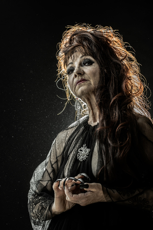 fingernail: One old scary smiling witch woman with long red knotty hair in blouse with black long nails on hand as halloween character with bright makeup in studio on black background, vertical photo
