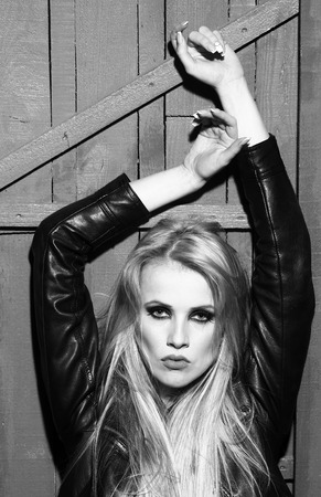 nackte brust: Portrait of one attractive sensual sexy young serious passionate blonde woman with long hair in leather black jacket and bare chest with raised hands in studio on wooden background, vertical picture Lizenzfreie Bilder