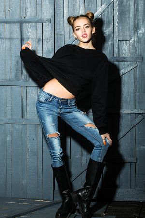 torn jeans: Full length view of one straight slender funny young smiling happy woman with cool hairstyle in torn jeans and black sweater with flexible body standing in studio on wooden backdrop, vertical picture Stock Photo